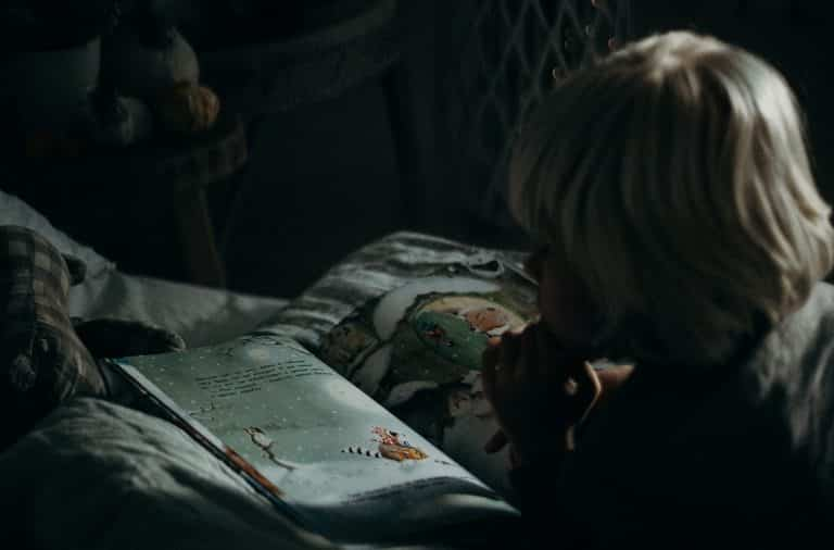 Child reading a book at night in the dark