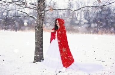 Woman in red robe in the snow outside