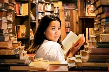 Woman with a sly smile in a bookstore