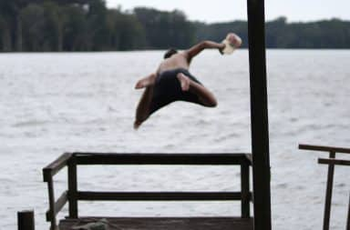 Teenage boy jumps into ocean from a dock