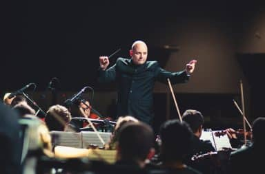 Conductor maestro on stage performing a symphony orchestra song