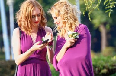 Two bridesmaids looking at a cell phone