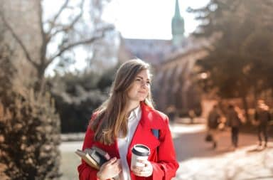 Woman on campus at small liberal arts college holding coffee and textbooks