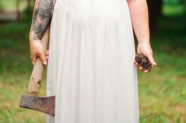 Woman in white dress holding an axe
