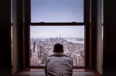 Man looking outside his apartment window at New York City