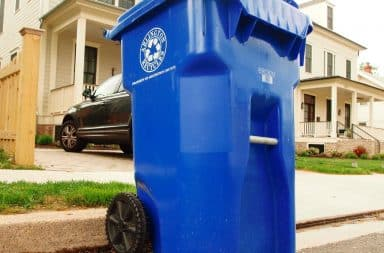 Recyling bin outside a house on the curb of street