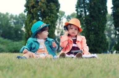 Toddlers sitting on the grass outside talking