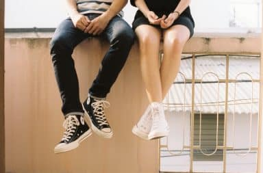 Teenage couple sitting on a building (legs only)
