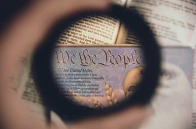 We the People on a passport with magnifying glass