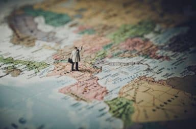 Man waving goodbye standing on a world map