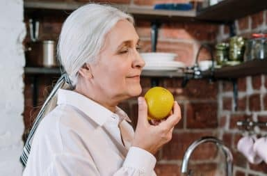 Sexy nymphomaniac grandmother smelling a lemon