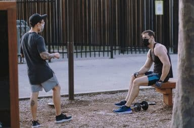 Two men with masks on outside working out