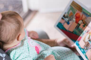 Baby reading book in bed