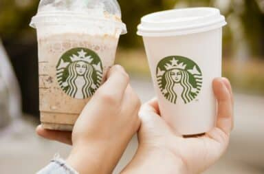 Two Starbucks cups held by a couple