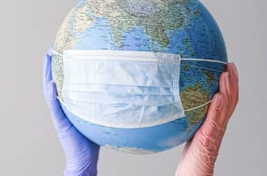 Globe with a medical mask on held up by two gloved hands