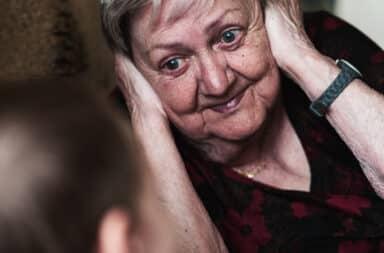 Grandmother covering her ears when grandson talks