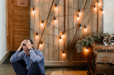 Man sitting down with hands on his head in front of a sliding barn door