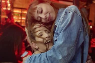 Two women in a bar hugging