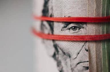 Abraham Lincoln peeking through a rubber band on a five dollar bill