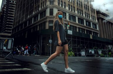 Woman wearing a mask apartment hunting in the city