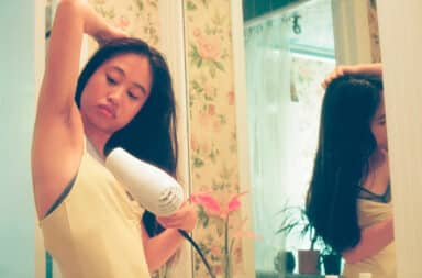 Woman blow drying underarm hair