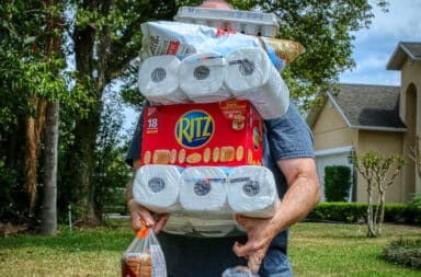 Grocery items stacked in hands of man