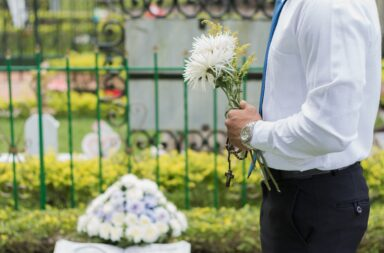 holding flowers graveside