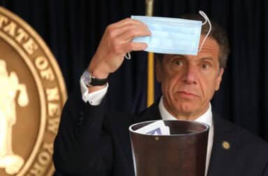 Cuomo puts a mask in a trash can