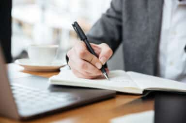 Hand writing an essay with paper and pen