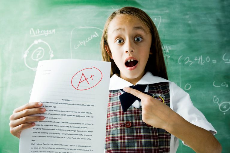 Girl holding A+ school paper