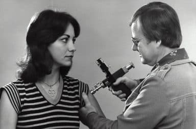 Man giving a vaccine into a woman's arm