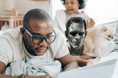Dad, child, Frankenstein, and laptop on the bed