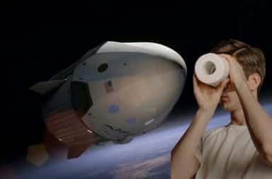 Man looking thru toilet paper roll at a spaceship