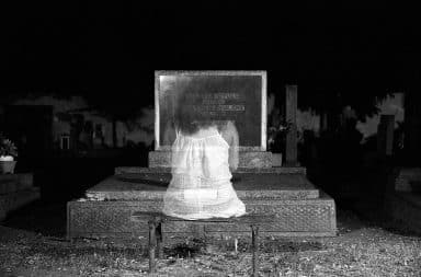 ghost in front of a gravestone