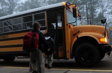 kid getting onto the school bus